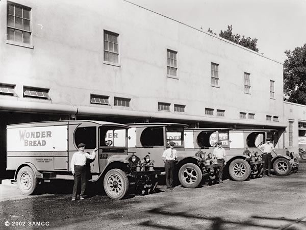 Photographic print of four Wonder Bread Bakery trucks parked in front of the loading dock.